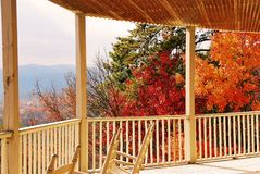 Autumn view from porch. Autumn view of mountains and valley from the front porch with rocking chairs and fall colors in view during early morning sunlight Royalty Free Stock Photos