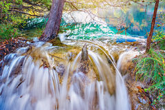 Autumn view of the small waterfall with pure water at sunset. Royalty Free Stock Photo