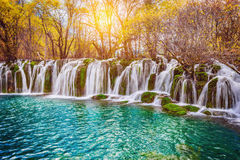 Autumn view of the waterfall with pure water at sunrise time. Royalty Free Stock Image