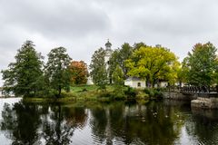 Autumn view of a white church located by a river. Colorful autumn view of a white church located by a river in Sweden. Green yellow and orange colored trees and Stock Photo