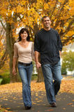 Autumn walk. A happy couple walks holding hands on an autumn day Stock Photography