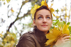Autumn walk. Portrait of a beautiful girl on a background of yellow leaves Royalty Free Stock Image