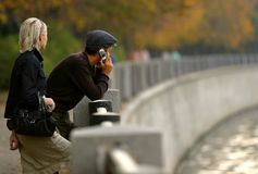 Autumn walk. The woman and the man with the phone on quay Stock Images