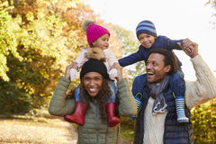 Autumn Walk With Parents Carrying Children On Shoulders Royalty Free Stock Photos
