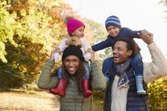 Autumn Walk With Parents Carrying-Kinder auf Schultern Lizenzfreie Stockfotos