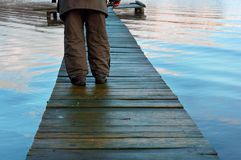 A pier in the lake, autumn walk on the wooden deck, walk along the river pier. Autumn walk on the wooden deck, a pier in the lake, walk along the river pier royalty free stock image