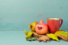 Autumn wallpaper with red tea cup, pomegranate and fall leaves. On wooden board stock image