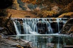 Autumn waterfall. Autumn leaves fallen on river waterfall stock image