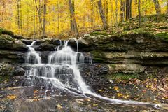 Autumn Waterfall at Tailwater. Tailwater Falls, a beautiful little waterfall in Owen County,  Indiana`s Lieber State Recreation Area, cascades through a colorful Royalty Free Stock Images