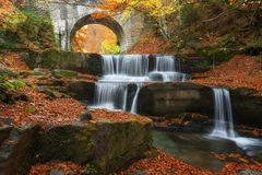 Autumn waterfalls near Sitovo, Plovdiv, Bulgaria. Beautiful cascades of water with fallen yellow leaves. Royalty Free Stock Image