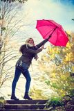 Woman walking in park with umbrella, strong wind Royalty Free Stock Photos