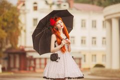 Autumn weather. Retro redhead girl in polka dots dress hold black umbrella. Raining in city. Wet umbrella against the backdrop of royalty free stock images