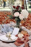 Autumn wedding table setting. Garden party celebration, picnic with golden cutlery, porcelain plate,wine glass and white
