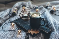 Autumn weekend concept. Still life details of living room. Cup of coffee on rustic wooden tray, candle and warm woolen sweater on sofa, decorated with led lights stock images