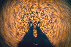 Autumn Wind Blowing Fallen Leaves que remolina alrededor de pies del hombre fotografía de archivo libre de regalías