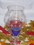 Autumn wine by candle light. Two glasses of wine one red,blue set among colourful autumn leaves by candle light Royalty Free Stock Images