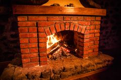 Autumn or winter burning fireplace cozy evening concept close up. Close up shot of burning firewood in the fireplace. Selective focus stock photo