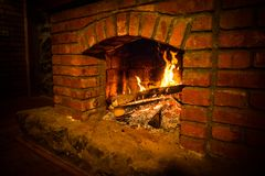 Autumn or winter burning fireplace cozy evening concept close up. Close up shot of burning firewood in the fireplace. Selective focus royalty free stock photo