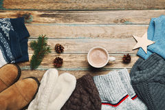 Autumn or winter clothes, sweater, shoes, mittens, fir tree and hot cocoa on wooden vintage background from above. Flat lay. Stock Photography