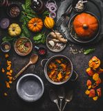 Autumn and winter cooking and eating with pumpkin dishes. Vegetarian stew in cooking pot with spoon and vegetables ingredients on. Dark kitchen table background stock photography