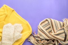Autumn winter fashion seasonal concept sweater cardigan Scandinavian knitted scarf and white fluffy homemade mittens. Fall on paper purple background Flat lay royalty free stock image