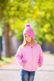 Autumn winter kid girl blond with jeans and pink snow cap Stock Photo