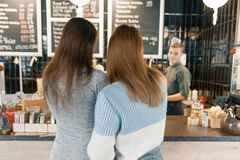 Autumn winter portrait of two young women standing with their backs near the bar counter in coffee shop, girls talking to a. Barista man stock photography