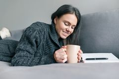 Autumn winter portrait of young girl in warm knitted sweater at home on sofa with notebook and cup of hot drink royalty free stock photo