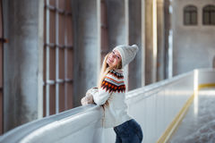 Autumn, Winter portrait: Young smiling woman dressed in a warm woolen cardigan, gloves and hat posing outside. Stock Photography