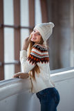 Autumn, Winter portrait: Young smiling woman dressed in a warm woolen cardigan, gloves and hat posing outside. Royalty Free Stock Image