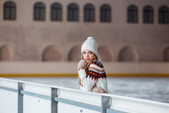 Autumn, Winter portrait: Young smiling woman dressed in a warm woolen cardigan, gloves and hat posing outside. Royalty Free Stock Photo