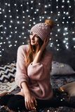 Autumn, Winter portrait: Young smiling woman dressed in a warm woolen cardigan and hat posing inside. Royalty Free Stock Photo