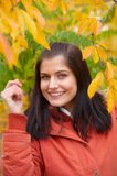 Autumn woman. Pretty girl and gold leaf Stock Image