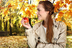 Autumn woman with apple. Portrait of a beautiful woman in autumn scenery Royalty Free Stock Image