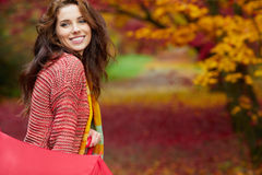 Autumn woman in autumn park with red umbrella, scarf and leather Royalty Free Stock Image