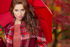 Autumn woman in autumn park with red umbrella, scarf and leather Stock Photos