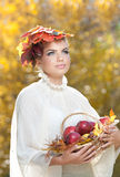 Autumn Woman. Beautiful creative makeup and hair style in outdoor shoot . Girl with leaves in hair holding a basket with apples Royalty Free Stock Image