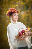Autumn Woman. Beautiful creative makeup and hair style in outdoor shoot . Girl with leaves in hair holding a basket with apples Stock Image