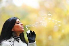 Autumn woman blow bubbles Royalty Free Stock Photos