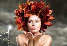 Autumn Woman Blowing Kiss auf bewölktem Himmel Schönes Art- und Weisebaumuster Lizenzfreies Stockfoto