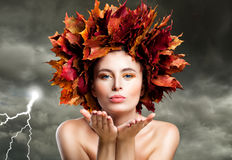 Autumn Woman Blowing Kiss on Cloudy Sky. Beautiful Fashion Model Royalty Free Stock Photo