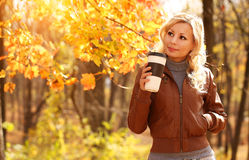 Autumn Woman with Coffee Cup. Fall. Blonde Beautiful Girl. And Yellow Leaves in the Park stock image