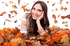 Autumn woman in a colorful pile of leaves royalty free stock photography