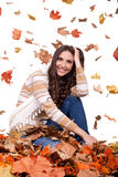 Autumn woman in a colorful pile of leaves Stock Photos