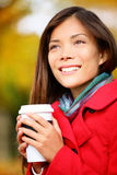 Autumn woman drinking coffee in fall city park. Or forest. Beautiful fall colors and happy smiling Asian girl drinking coffee or tea from disposable cup outdoor Stock Images