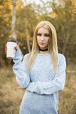 Autumn woman drinking coffee. Fall concept of young woman enjoying hot drink from disposable coffee cup royalty free stock photos