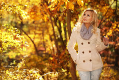 Autumn Woman. Fall. Blonde Beautiful Girl with Yellow Leaves stock photos