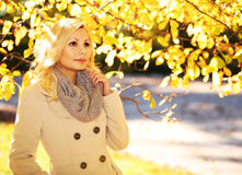 Autumn Woman. Fall. Blonde Beautiful Girl with Yellow Leaves Royalty Free Stock Images