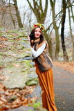Autumn woman with flowers wreath near a stone wall Royalty Free Stock Image
