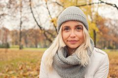 Autumn woman in grey knitted hat and scarf outdoors. Cute girl walking in fall park stock photo